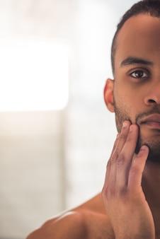 Homem afro-americano considerável que toca em sua cara.