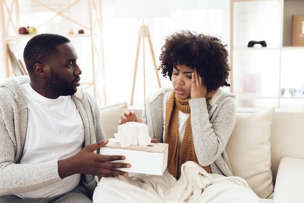 Homem afro-americano dá guardanapos a mulher doente no lenço.