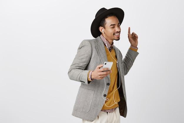 Homem afro-americano dançando despreocupado, ouvindo música em fones de ouvido, sorrindo e segurando um smartphone