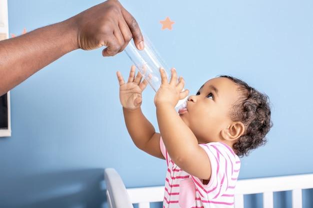 Homem afro-americano dando água para seu lindo bebê em casa