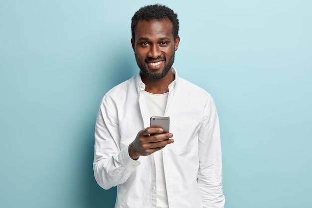 Homem afro-americano de camisa branca segurando o telefone