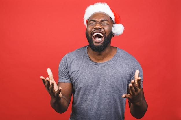 Homem afro-americano de camiseta cinza e chapéu de papai noel