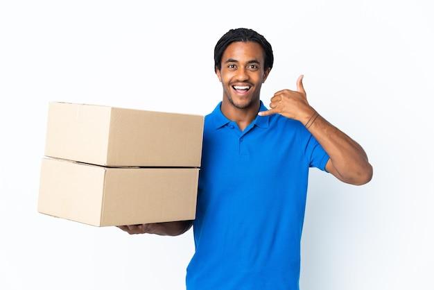 Homem afro-americano de entrega com tranças isoladas no fundo branco, fazendo gesto de telefone. ligue-me de volta sinal