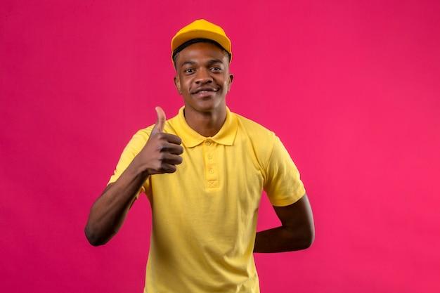 Homem afro-americano de entrega em camisa pólo amarela e boné, sorrindo amigável mostrando os polegares para cima na rosa