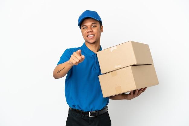 Homem afro-americano de entrega isolado no fundo branco surpreso e apontando para a frente