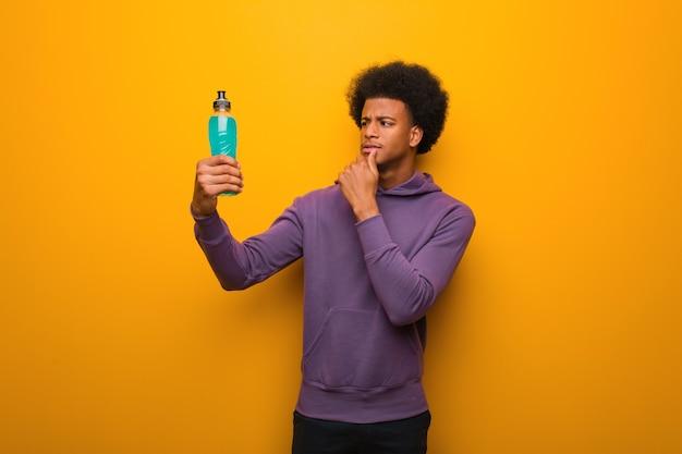 Homem afro-americano de fitness segurando uma bebida energética, duvidando e confuso