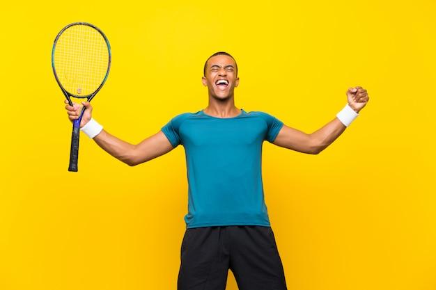 Homem afro-americano de jogador de tênis sobre fundo amarelo isolado
