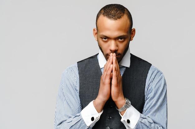 Homem afro-americano de mãos dadas em oração, esperando por melhor.