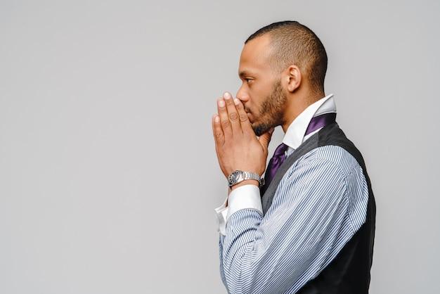 Homem afro-americano de mãos dadas em oração
