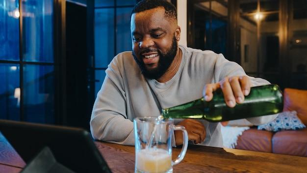 Homem afro-americano de meia-idade, bebendo cerveja, se divertindo com a celebração on-line do evento da festa à noite feliz por meio de videochamada na sala de estar em casa.