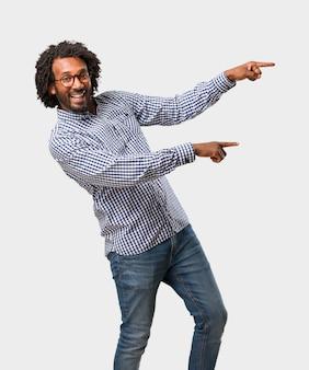 Homem afro-americano de negócios bonito, apontando para o lado, sorrindo surpreendeu a apresentação