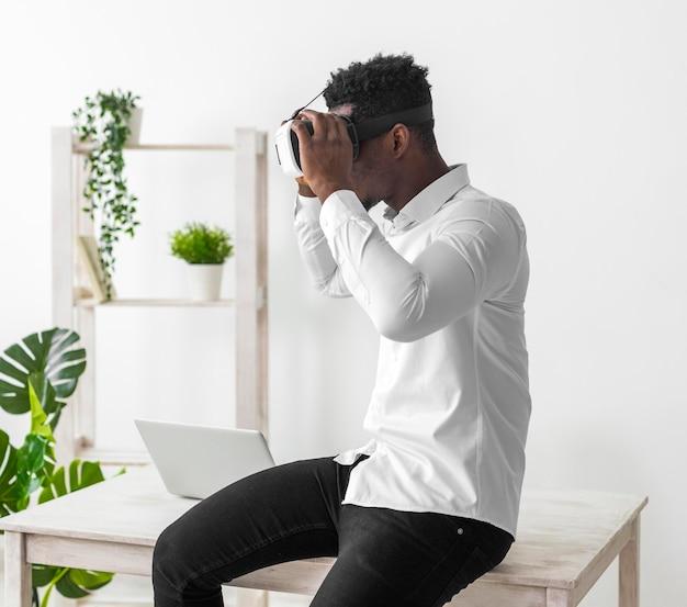 Homem afro-americano de negócios de vista lateral usando o conjunto de vr