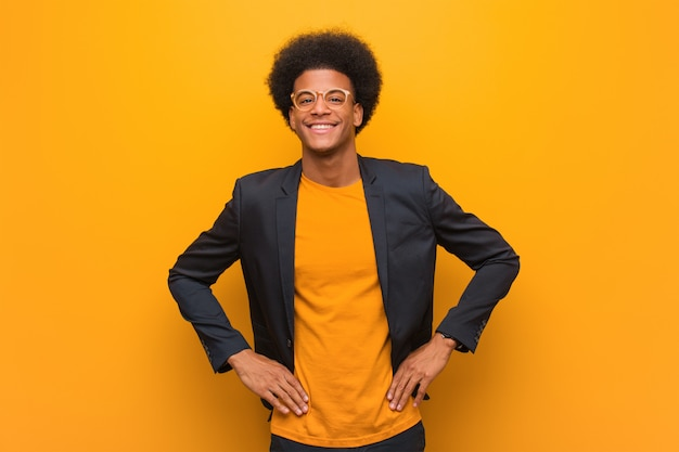 Homem afro-americano de negócios jovem ao longo de uma parede laranja com as mãos nos quadris