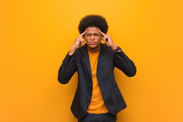 Homem afro-americano de negócios jovem ao longo de uma parede laranja, fazendo um gesto de concentração