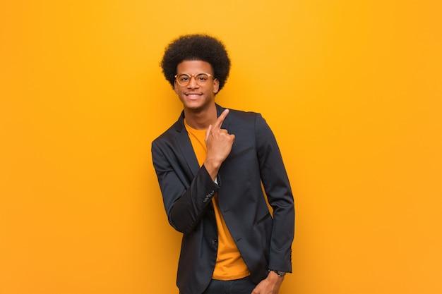 Homem afro-americano de negócios jovem ao longo de uma parede laranja, sorrindo e apontando para o lado