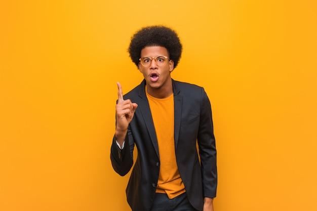 Homem afro-americano de negócios jovem ao longo de uma parede laranja, tendo uma idéia, conceito de inspiração