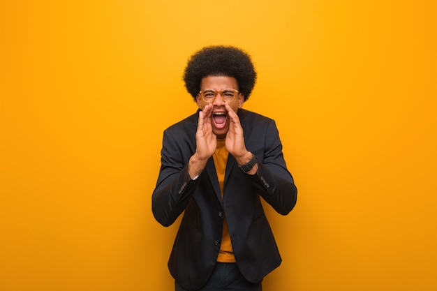 Homem afro-americano de negócios jovem sobre uma parede laranja gritando algo feliz para a frente