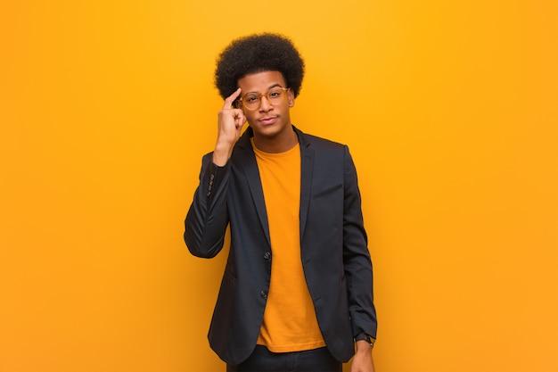 Homem afro-americano de negócios jovem sobre uma parede laranja, pensando em uma idéia
