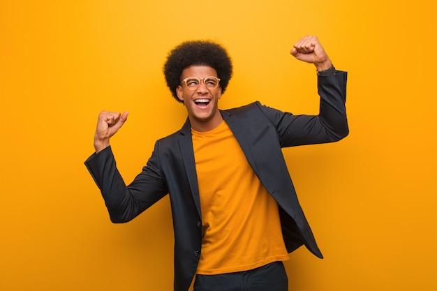 Homem afro-americano de negócios jovem sobre uma parede laranja que não se rende