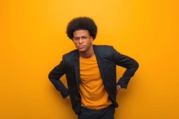 Homem afro-americano de negócios jovem sobre uma parede laranja repreendendo alguém muito zangado