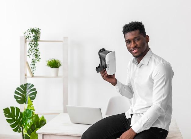 Homem afro-americano de negócios segurando um conjunto de vr