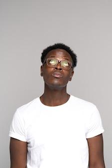 Homem afro-americano de óculos usa camiseta branca pensando, olhando para o espaço da cópia, isolado