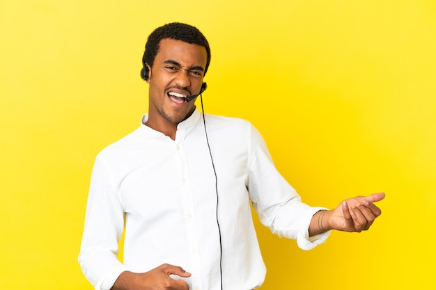 Homem afro-americano de telemarketing trabalhando com um fone de ouvido sobre um fundo amarelo isolado, fazendo gestos de guitarra