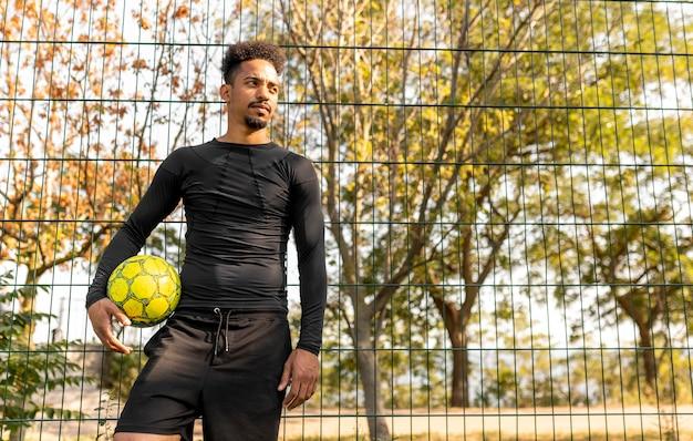 Homem afro-americano de tiro certeiro posando com uma bola de futebol e espaço de cópia