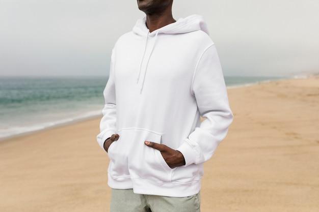 Homem afro-americano descolado com capuz branco em uma sessão de fotos de inverno na praia
