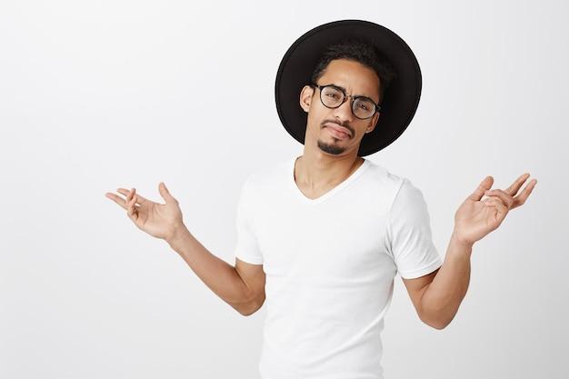 Homem afro-americano descuidado e desinteressado, de chapéu e óculos, mãos abertas para os lados