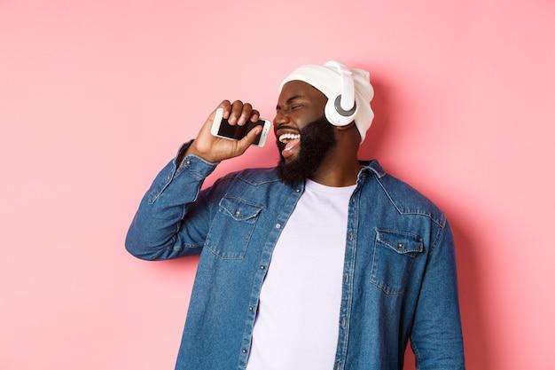 Homem afro-americano despreocupado ouvindo música em fones de ouvido, cantando no celular como um microfone, em pé sobre um fundo rosa