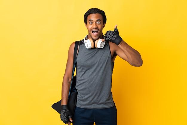 Homem afro-americano do esporte jovem com tranças com saco isolado na parede amarela, fazendo gesto de telefone. ligue-me de volta sinal