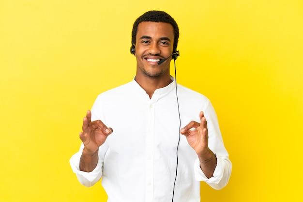 Homem afro-americano do operador de telemarketing trabalhando com um fone de ouvido sobre um fundo amarelo isolado, mostrando um sinal de ok com os dedos