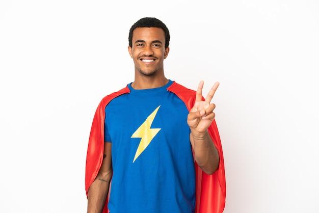 Homem afro-americano do super-herói sobre fundo branco isolado, sorrindo e mostrando sinal de vitória