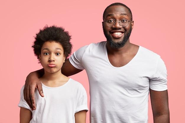 Homem afro-americano e criança em camisetas brancas