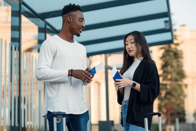 Homem afro-americano e mulher asiática, segurando passaportes e falando no ponto de ônibus.
