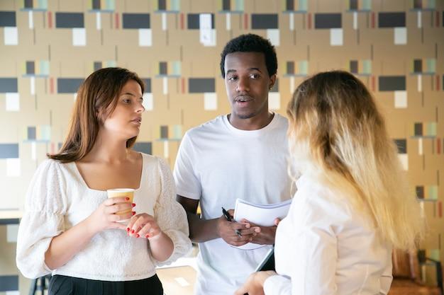 Homem afro-americano e senhora branca olhando para uma mulher loira