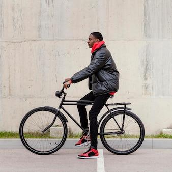 Homem afro-americano e sua bicicleta.