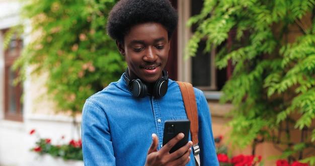 Homem afro-americano elegante com cabelo castanho, usando seu smartphone para a videochamada enquanto caminha.