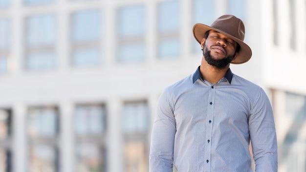 Homem afro-americano elegante posando ao ar livre com espaço de cópia