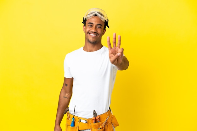Homem afro-americano, eletricista em uma parede amarela isolada, feliz e contando três com os dedos