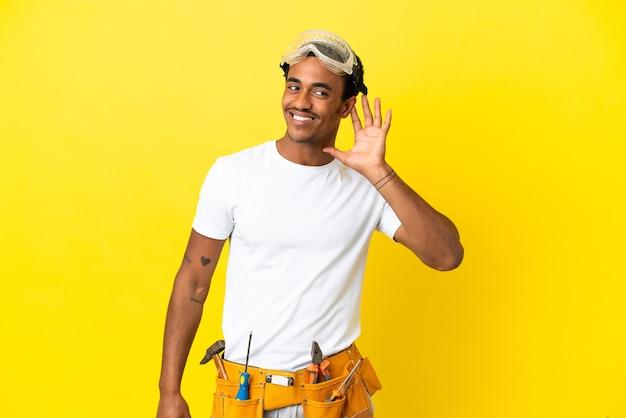 Homem afro-americano, eletricista em uma parede amarela isolada, ouvindo algo colocando a mão na orelha
