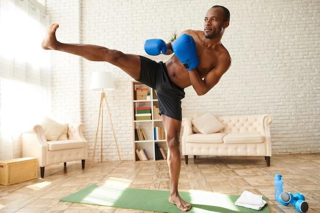 Homem afro-americano em luvas de boxe faz chute.