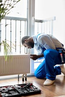 Homem afro-americano em macacão de trabalho usando ferramentas durante a instalação do radiador de aquecimento na sala
