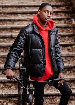 Homem afro-americano em plano médio e sua bicicleta