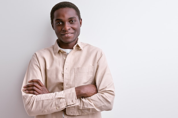 Homem afro-americano em roupa casual sorrindo para a câmera com um rosto agradável, homem de bom humor, retrato isolado