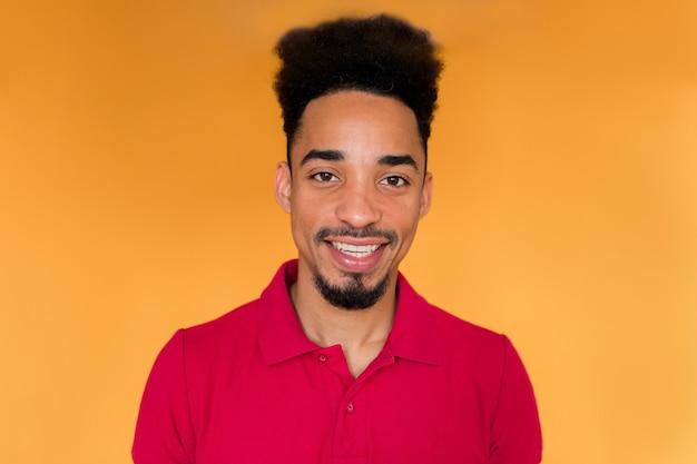 Homem afro-americano em t-shirt vermelha e sorrindo sobre a parede amarela.