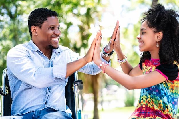 Homem afro-americano em uma cadeira de rodas curtindo e se divertindo com a filha no parque