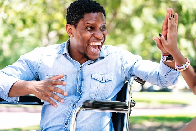 Homem afro-americano em uma cadeira de rodas, curtindo e se divertindo com a filha no parque.