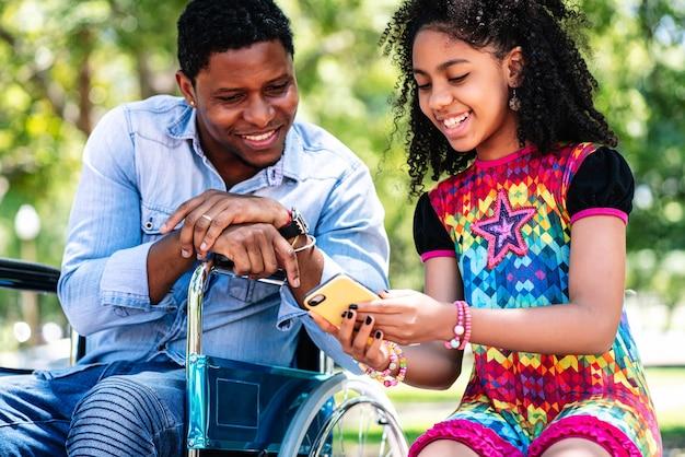 Homem afro-americano em uma cadeira de rodas, usando um telefone celular com a filha, enquanto desfruta de um dia juntos no parque.
